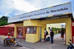 Fachada externa da universidade. Dois portões grandes, um deles está aberto. Entre os portões uma guarita. Sobre os portões e a guarita, no alto o nome: Universidade Estadual da Região Tocantina do Maranhão. Em frente ao portão estão três pessoas. No meio-fio um motoqueiro do serviço de moto-táxi espera um passageiro.