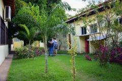 Área interna da universidade entre dois blocos, com ajardinamento onde se vê flores, gramado e alguns arbustos. Um casal caminha abraçado pelo gramado, tendo mochilas nas costas.