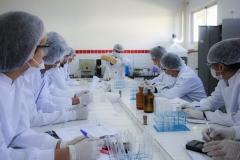 Estudantes vestidos com jalecos brancos, de luvas, máscaras e touca se encontram dentro de um laboratório da universidade, ao redor de uma bancada. Sobre a bancada estão alguns tubos de ensaio e alguns vidros.