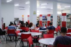 Interior da biblioteca da universidade. Mesas redondas com cadeiras vermelhas acomodam estudantes que leem e fazem pesquisas. Ao fundo se observa as prateleiras de livros.