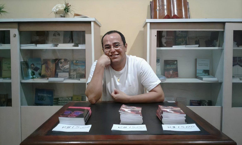 O professor Marcos Fábio aparece sentado atrás de uma mesa que contém três pilhas de livros.