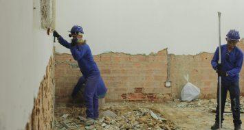 Trabalhadores pedreiros quebram o reboco de uma parede.