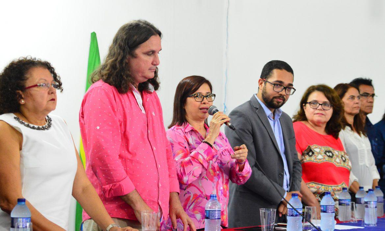 Professores que compõem a Gestão Superior da UEMASUL aparecem em pé, atrás de uma mesa, enquanto a Reitora fala segurando um microfone.