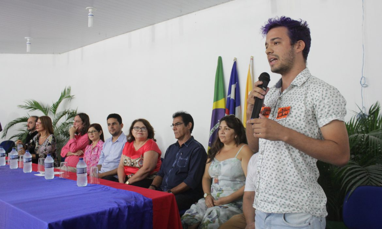 Um estudante, que tem adesivos do grupo Juventude Anticapitalista colados em sua camisa, fala ao microfone ao lado da mesa da gestão superior da UEMASUL.