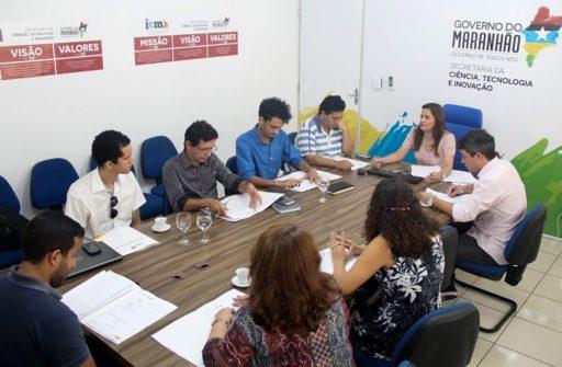 Um grupo de pessoas aparece sentado ao redor de uma mesa em reunião.