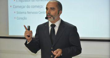 O professor Allan Kardec Duailibe Barros Filho aparece em frente a um quadro branco ministrando aula.