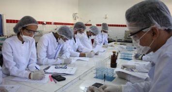 Estudantes em laboratório da UEMASUL realizam procedimentos científicos.