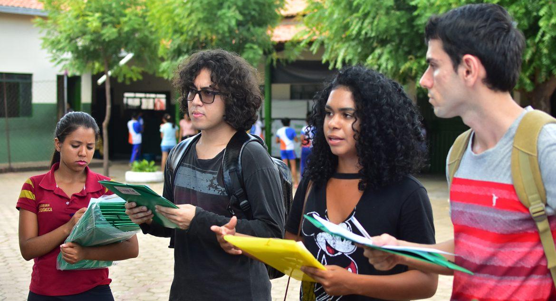Na foto, um grupo de jovens acadêmicos está reunido no pátio de uma escola, conversando. Ao fundo se vê algumas árvores. Dois estudantes estão de costas, e os outros quatro de frente.
