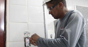 Eletricista instala sensor de movimento em banheiro.