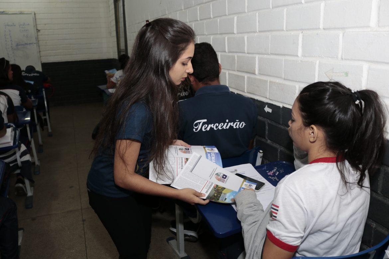 Integrante da equipe de Pró-reitoria da UEMASUL entrega uma edição da revista sobre a universidade para uma aluna.