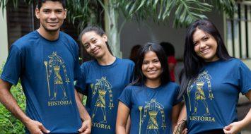 Acadêmicos do curso de História exibem posam para foto com as camisetas do curso.