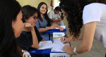 Participantes do evento e uma pessoa da comissão confirmando a presença dos mesmos via assinatura.