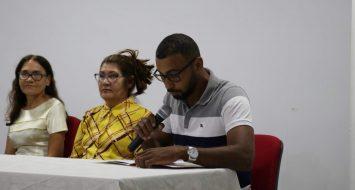 Sentados à mesa do auditório da UEMASUL, à direita duas professoras, à esquerda o acadêmico, com microfone na mão, lendo seu discurso.