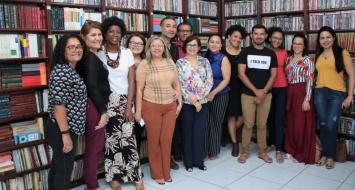 Professores reunidos em biblioteca discutem curricularização da extensão.