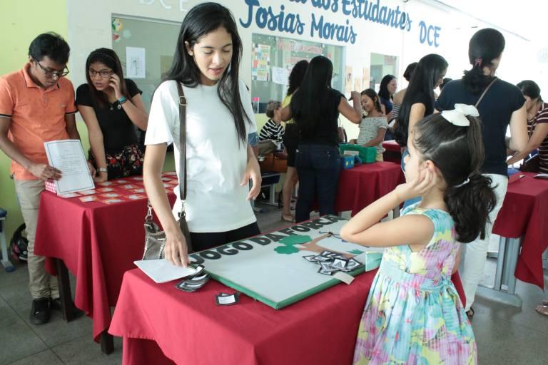 Acadêmica do curso de Pedagogia com uma criança perto de um jogo que se encontra em uma mesa.