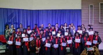 Turma de formandos da UATI reunidos no palco e apresentando seus diplomas de conclusão graduação.