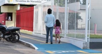 Uma mulher adulta caminha pela calçada tátil da UEMASUL de mãos dadas com uma criança.