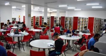Cerca de 10 alunos estão sentados nas messas estudando na biblioteca da UEMASUL.