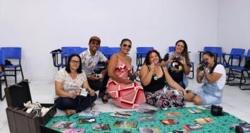Seis professores sentados no chão, em uma sala de aula, seguram objetos e livros usados na formação.