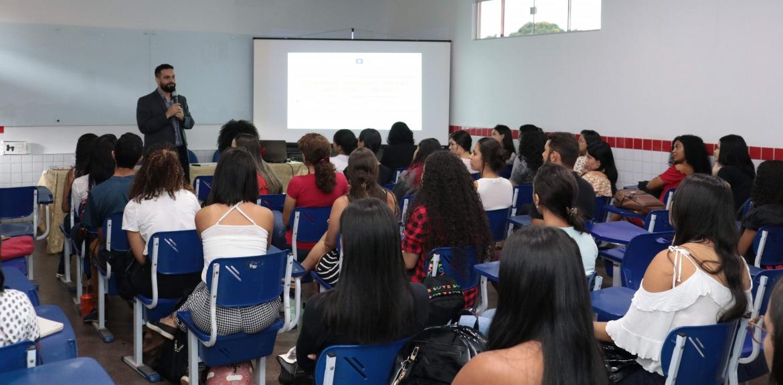 Homem em pé ministrando uma palestra para alunos sentados em uma sala de aula