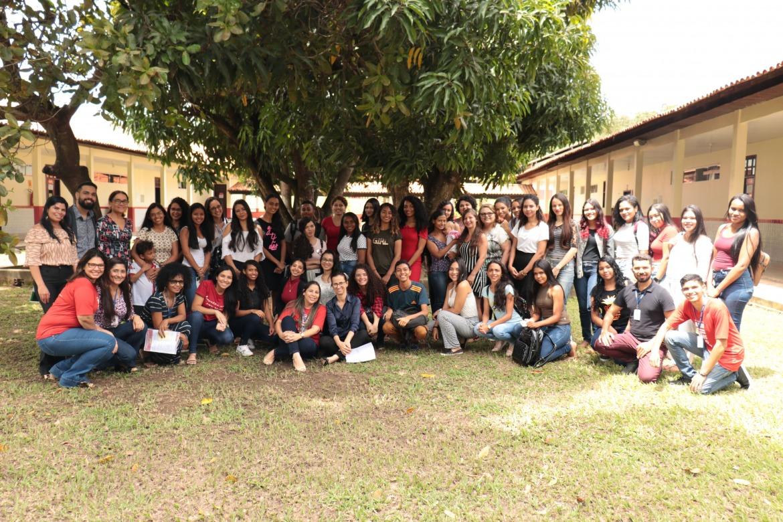 Os alunos da primeira turma de pedagogia aparecem posando debaixo de uma mangueira no pátio da universidade