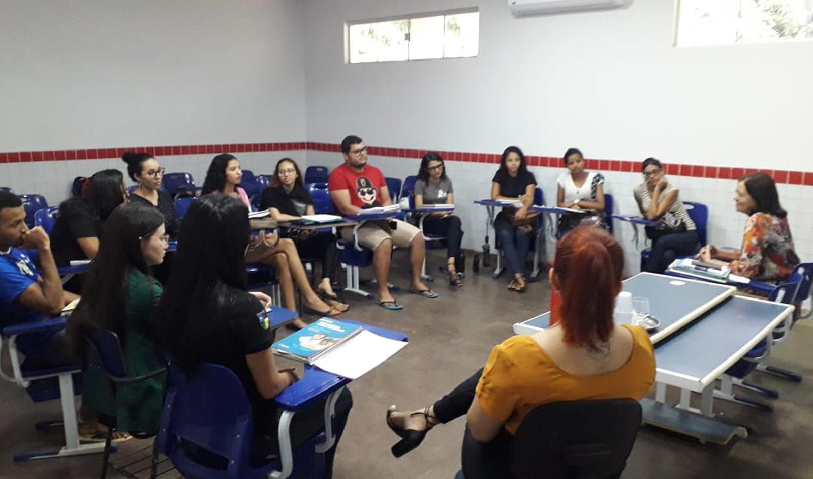 Grupo de pessoas em sala de aula, sentadas em círculo.