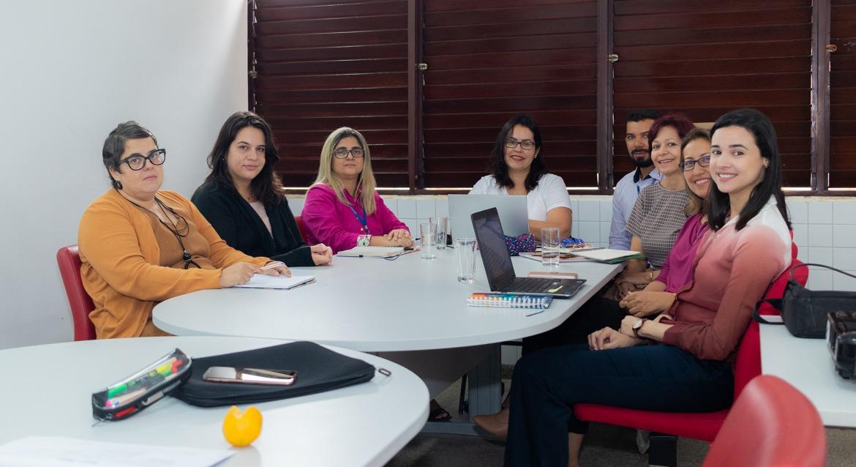 Oito pessoas sentadas à mesa de reunião, posam para foto e sorriem.