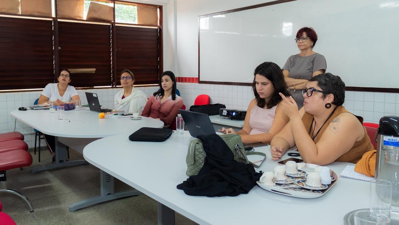 Seis mulheres, cinco sentadas em volta de uma mesa e uma em pé.