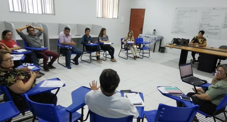 Cerca de 15 professores e professoras estão sentados em círculo para uma reunião.
