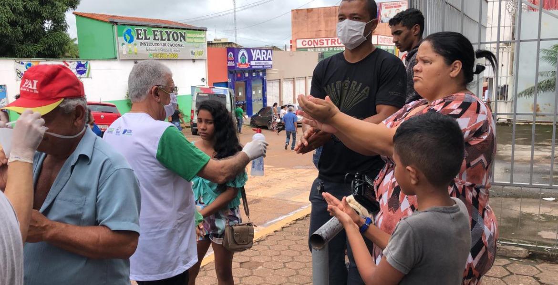 Pessoas na rua, com máscaras usam álcool gel nas mãos.
